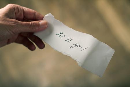 Mano que sostiene una nota de papel con el mensaje que le permita irse escrito en él Foto de archivo
