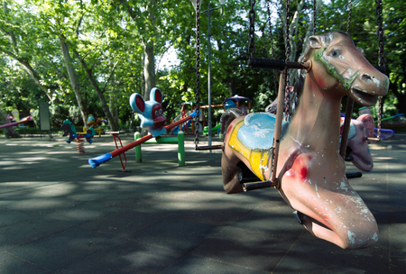 chain swing ride: horizontal close up of a toy horse with chains in an empty children playground