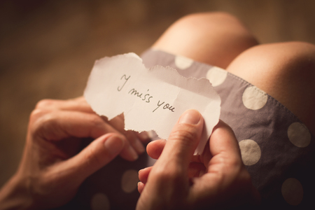 i miss you: Top view of woman in dotted dress holding a paper message with the text I miss you