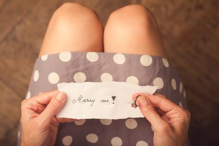メッセージで紙のメモを持っている手と彼女の指のリング結婚します。