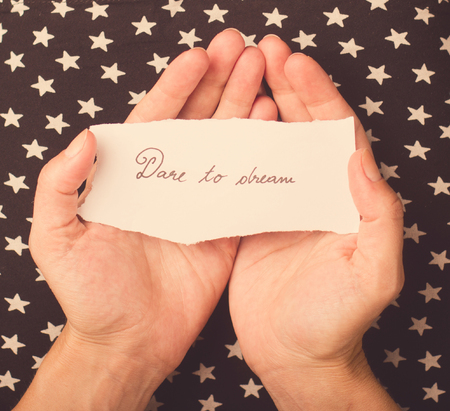 dare: Woman with star patterned dress holding a note with dare to dream message on it Stock Photo