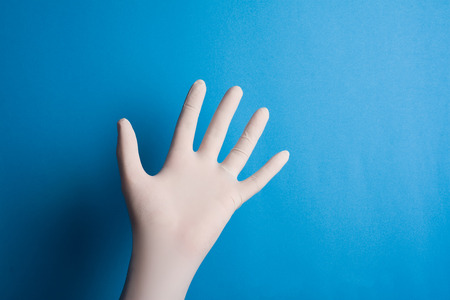 white glove: Horizontal front view of hand with surgical white glove on blue background Stock Photo