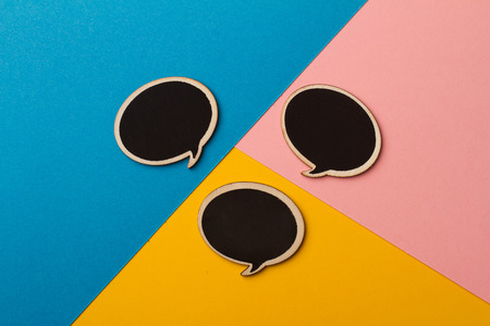 communication metaphor: Top view of round chalk board speech bubbles on colored papers, metaphor, concept for communication