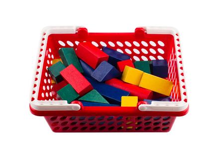 Vista frontal del carrito de compras de plástico rojo con bloques de construcción de madera de colores aislados en blanco Foto de archivo