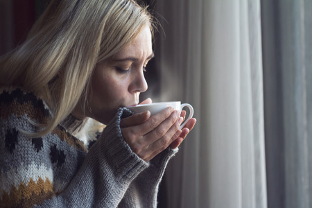 Blonde woman with long hair and warm sweater drinking a cup of hot steamy coffee in the morning by the window Stock Photo