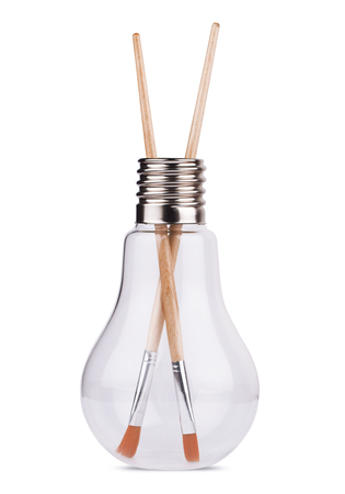 front view of a large light bulb with two painting brushes inside, concept for ideas, creativity. Isolated on white.