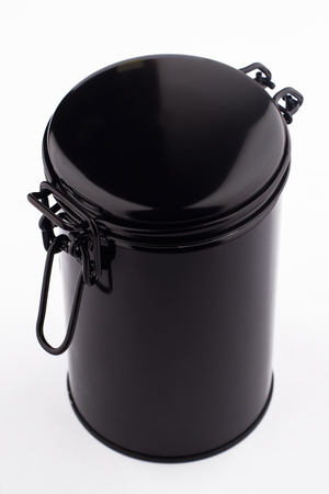 tinned goods: top view of black metal thin can container cylinder form for tea or coffee packaging isolated on white