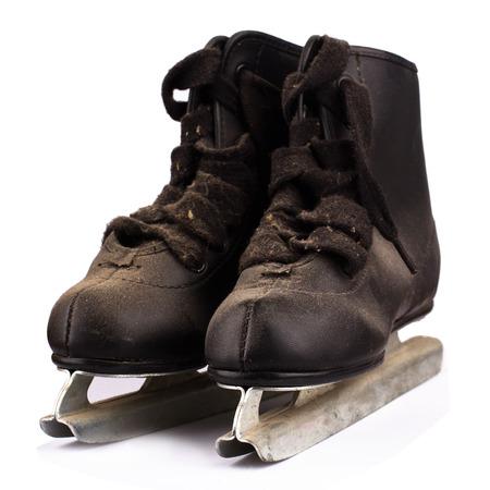 zapatos escolares: vista frontal de un par de niños pequeños patines de hielo negro cubierto de polvo aisladas sobre fondo blanco