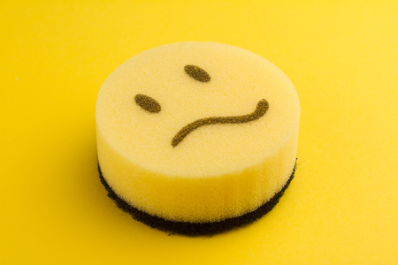 dish washing concept yellow sponge with sad scared face Stock Photo