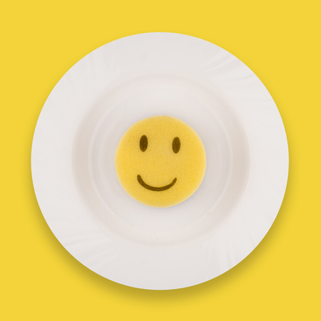 top view dish washing concept yellow sponge with happy face on a clean white meal plate
