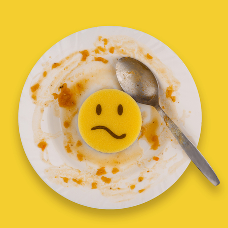 disgusted: top view dish washing concept yellow sponge with sad face on a dining white plate and spoon with food remains Stock Photo