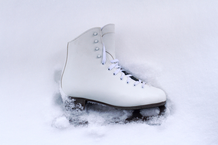 winterday: front view of white classical leather iceskate shoe with the metallic blade partially covered in snow