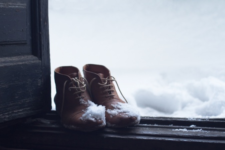 come home: front view of a pair of vintage brown leather shoes by the house wooden open door entrance covered in snow in winter time Stock Photo