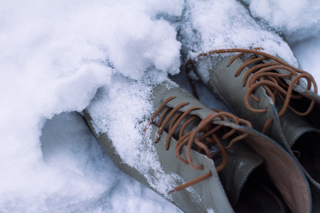 top view close up of a pair of vintage grey leather shoes with brown shoelaces covered in snow in winter time