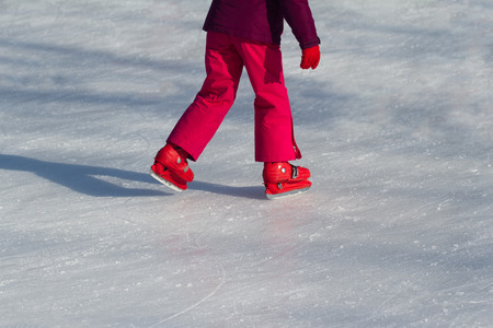 Side view close up of a child in red clothing and iceskates skating on ice rink in wintertime