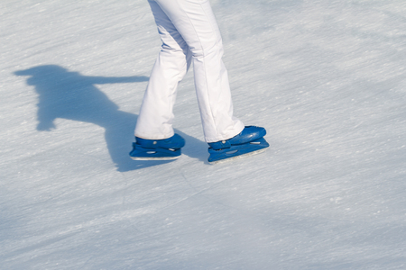 winterday: Side view close up of woman in white ski pants and blue iceskates skating on ice rink in wintertime