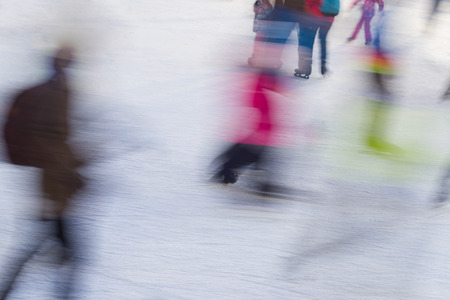 winterday: motion blur of different people skating on ice rink in the winter Stock Photo