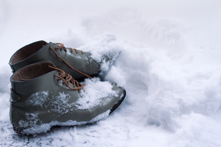 side view close up of a grey pair of vintage brown leather shoes covered in snow in winter time
