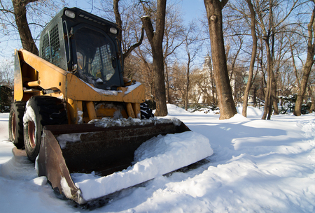 horizontal front view of a small empty tractor with snowplough covered in snow in the park, wintertime Stock Photo