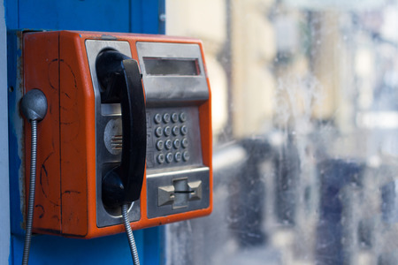 metallic button: Vertical side view of damaged orange public phone with near a dirty window with selective focus