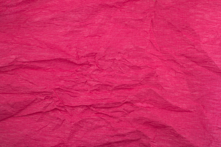 front view of crumpled paper background texture made from a dark pink sheet of wrapping paper Stock Photo
