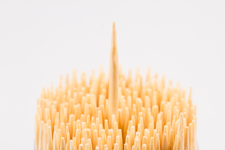 toothpick: horizontal top view close up of wooden bamboo toothpicks with one stick rising up isolated on white background