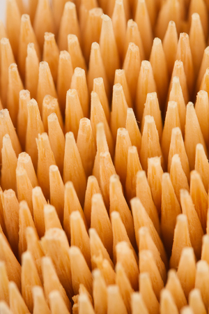 yellow teeth: vertical top view macro close up of wooden bamboo toothpicks pattern with selective focus