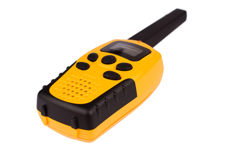 low angle of yellow walkie talkie with black keypad isolated on white background