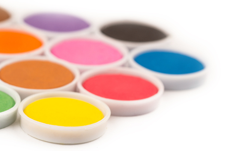 low angle closeup of water color palette in white plastic containers isolated on white selective focus