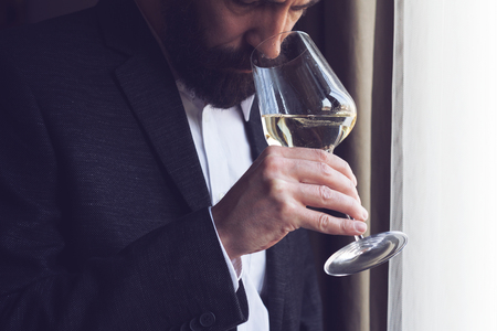 窓の自然な照明で白ワインを試飲ひげ黒のスーツと白いシャツと、白人男性の横がクローズ アップ 写真素材