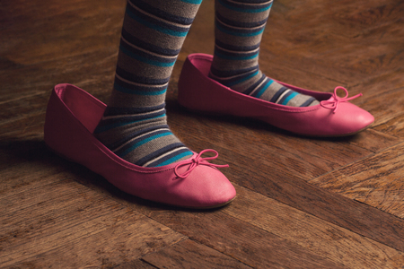 low angle closeup of child feet with stripe cotton stockings wearing large adult pink ballerina shoes on wood floor