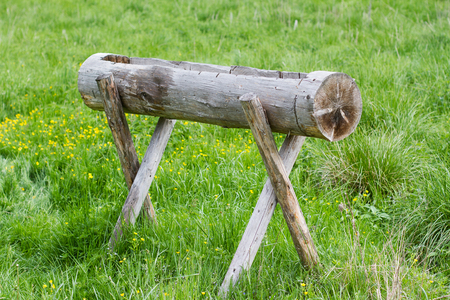 horizontal front view of hand made rustic animal water well made of wood on green field of grass Stock Photo