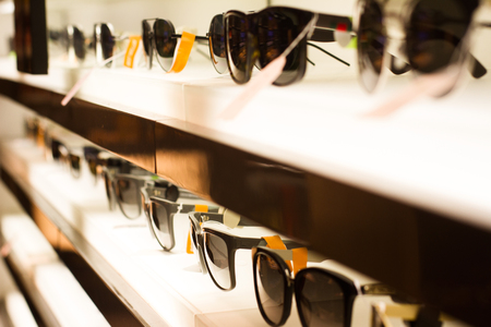 perspective view of many sun glasses on display on a store shelf selective focus