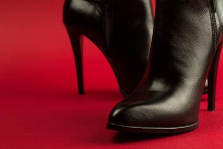 Horizontale Nahaufnahme der High Heel Frau schwarz Leder Herz Schuhe auf rotem Hintergrund