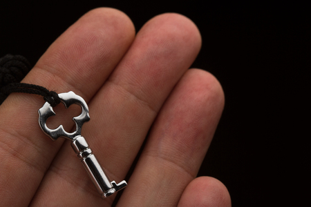 top view closeup of Caucasian hand holding a small silver lock key with dark fabric thread on black background