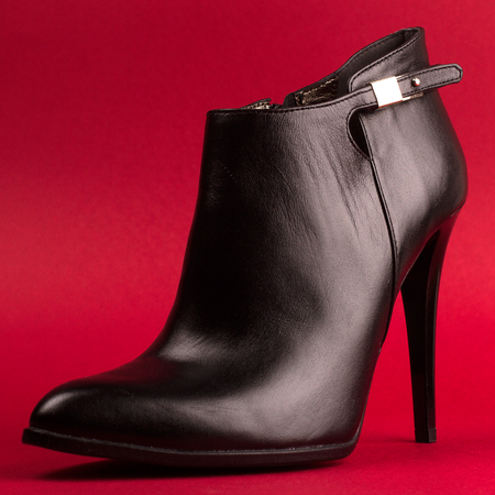 side view of high heel woman black leather stylish shoe on red background Stock Photo