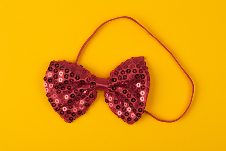 red bow tie with shinny and glittering spangles on light yellow background