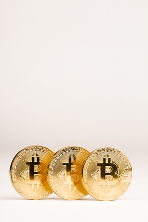 vertical front view closeup of bitcoin golden metallic coin on white background