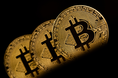 horizontal front view closeup of bitcoin golden metallic coins on dark background Stock Photo