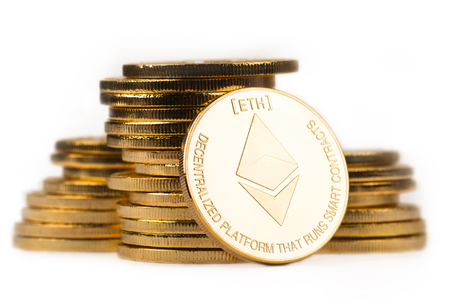 close up golden ethereum in front of a pile of golden metallic coins isolated on white background Stock Photo