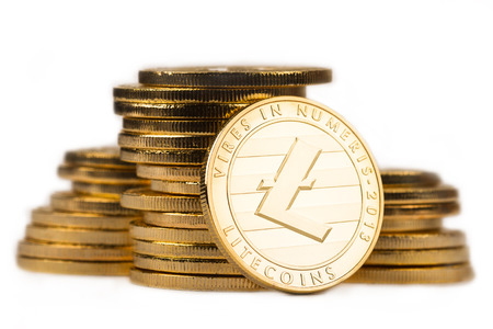 close up golden litecoin in front of a pile of golden metallic coins isolated on white background