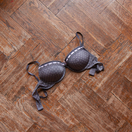 Top view of women bras in different colors thrown on the wooden floor