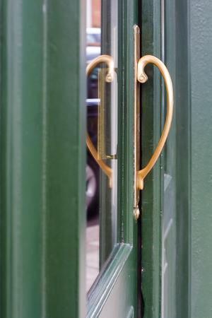 Side view of English pub green door golden handle