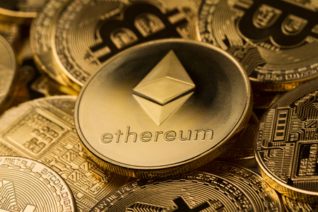 horizontal top view close up of metallic ethereum on a stack of bitcoin golden coins