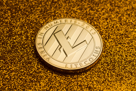 horizontal top view of single litecoin coin on golden glittering background texture concept for rich