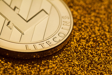Horizontal top view detail closeup of single lite coin on golden glittering background texture concept for rich
