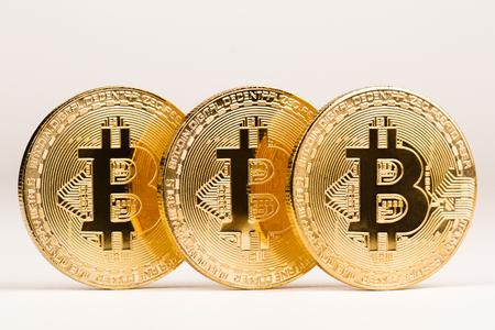 horizontal front view closeup of bitcoin golden metallic coin on white background