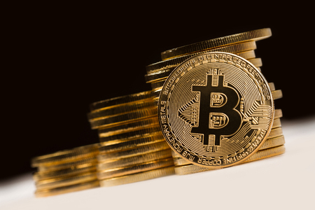close up golden bitcoin in front of a pile of golden metallic coins on black dark background