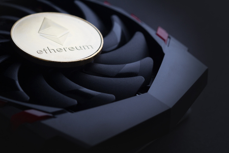 cryptocurrency mining concept with one golden Ethereum coin on top of a computer performant video card black fan