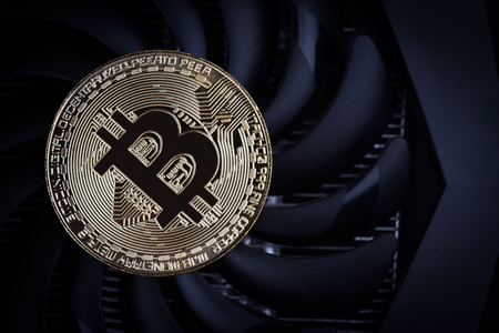 cryptocurrency mining concept top view closeup with one golden bitcoin on top of a computer performant video card black fan Stock Photo